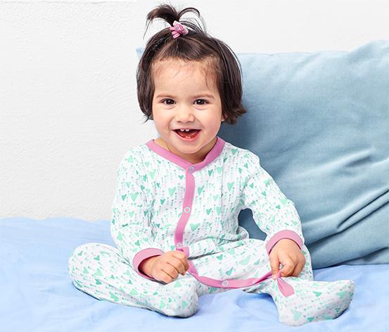Lachendes Kind sitzt auf Bett
