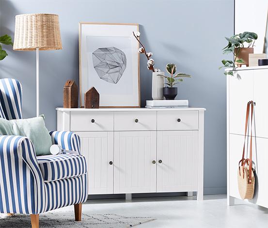 Biała szafka typu sideboard z półkami o regulowanej wysokości i dekoracyjnymi drzwiami listwowymi